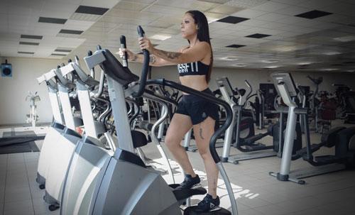 une femme s'entraine dans une salle de sport sur une machine de cardio chez Body Staff Gym salle de sport à Artigues-près-Bordeaux